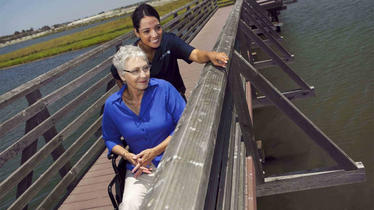 An Amada Senior caregiver with a senior on a bridge looking at a marsh in South Carolina