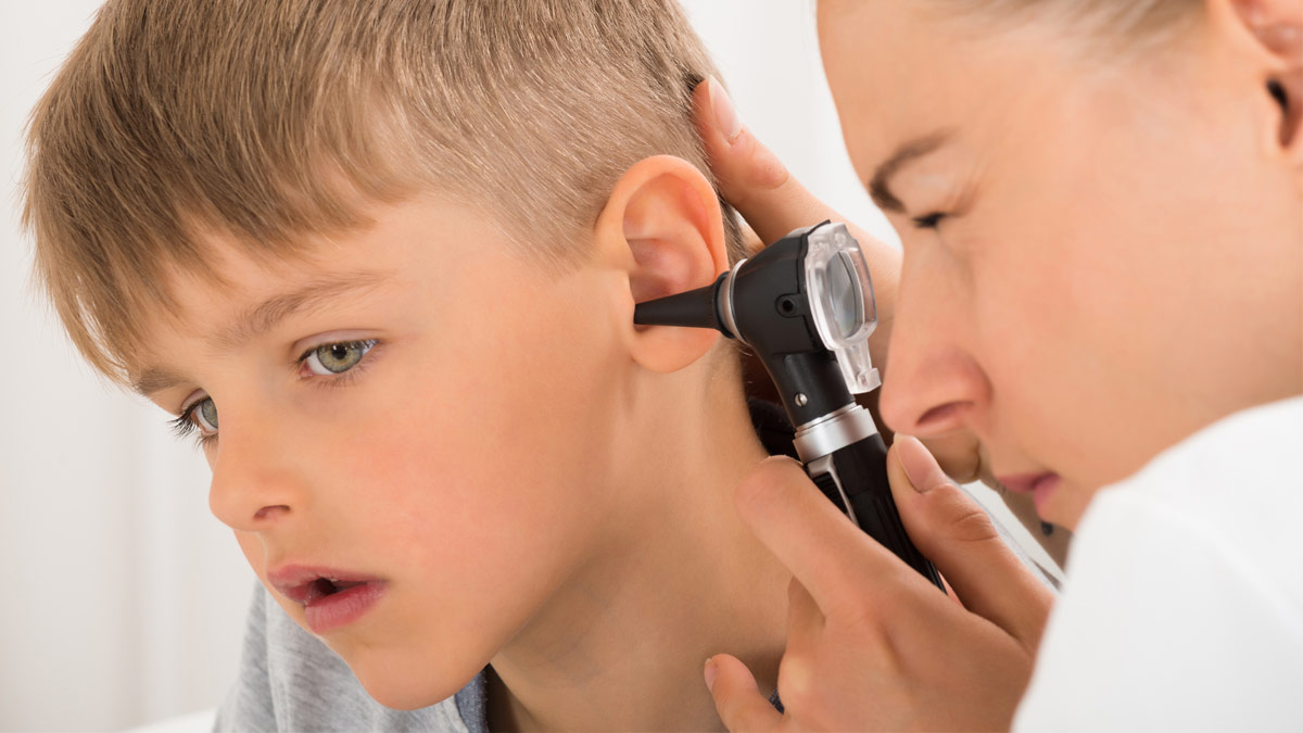 An ENT doctor examines a young boy's ears