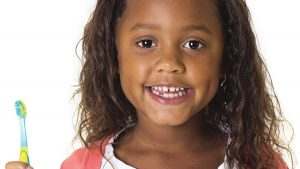 A young girl with a toothbrush smiling. February is National Children's Dental Health Month photo.