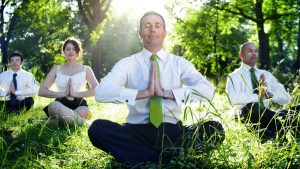 A group takes a break from work to meditate.