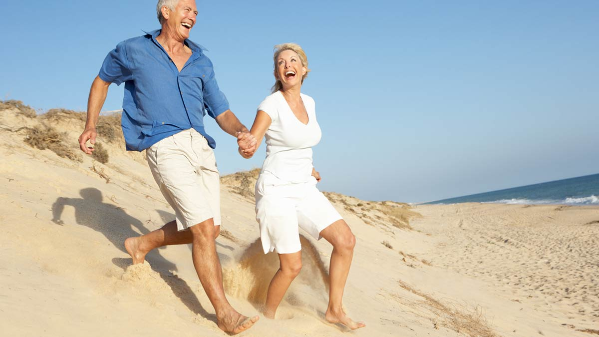 Senior couple running on the beach. On the Quest to a Better Life. Better Life Carolinas Seeks to Optimize Wellness.
