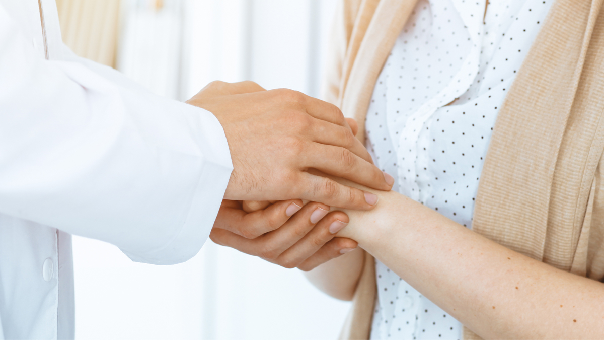 A doctor reassures a patient