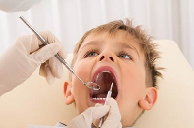 A young boy getting a dental exam. February is National Children's Dental Health Month photo.