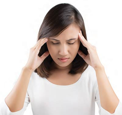 Photo of a woman with a headache. Botox is also used in the treatment of chronic migraines and tension headaches.