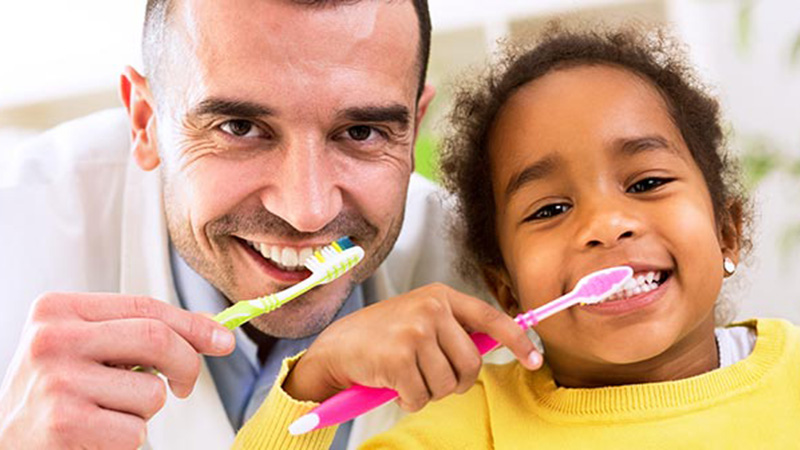A dentist and young girl brushing their teeth.