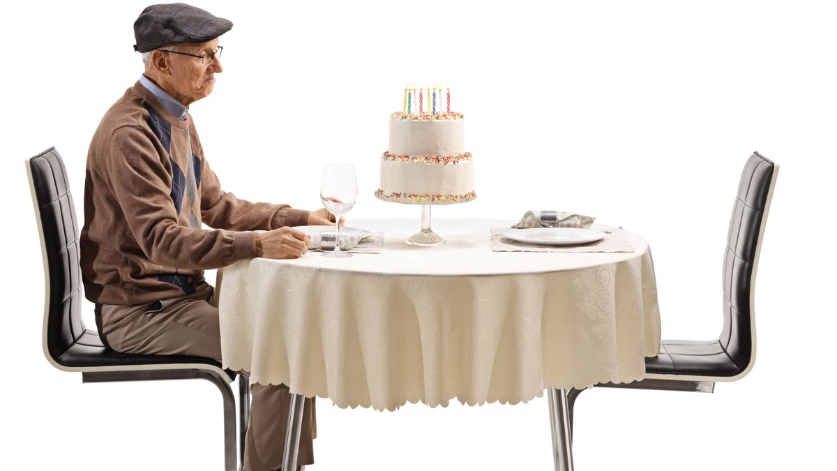 A lonely senior citizen sitting and staring at a birthday cake.