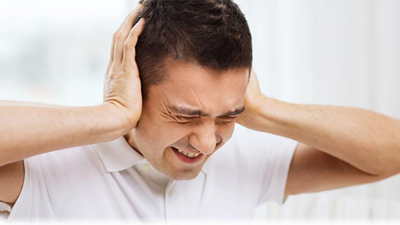 Loud noise causes a man to cover his ears and wince in pain
