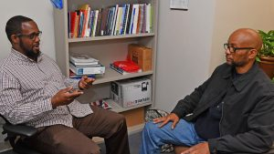 Peer Support Specialist Tyrone Jarmon, left, talks with veteran Gary Chapman.
