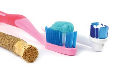 Oral hygiene through the years. A branch, a toothbrush and an electric toothbrush.