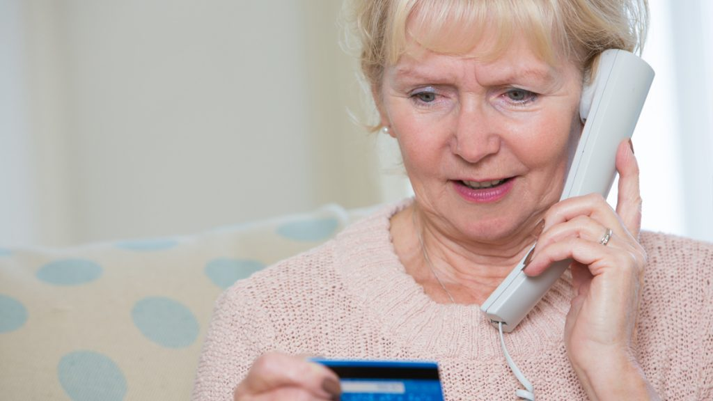 A woman on the phone giving credit card information to scammers