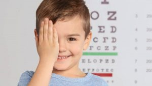A young boy smiles for a vision screening test