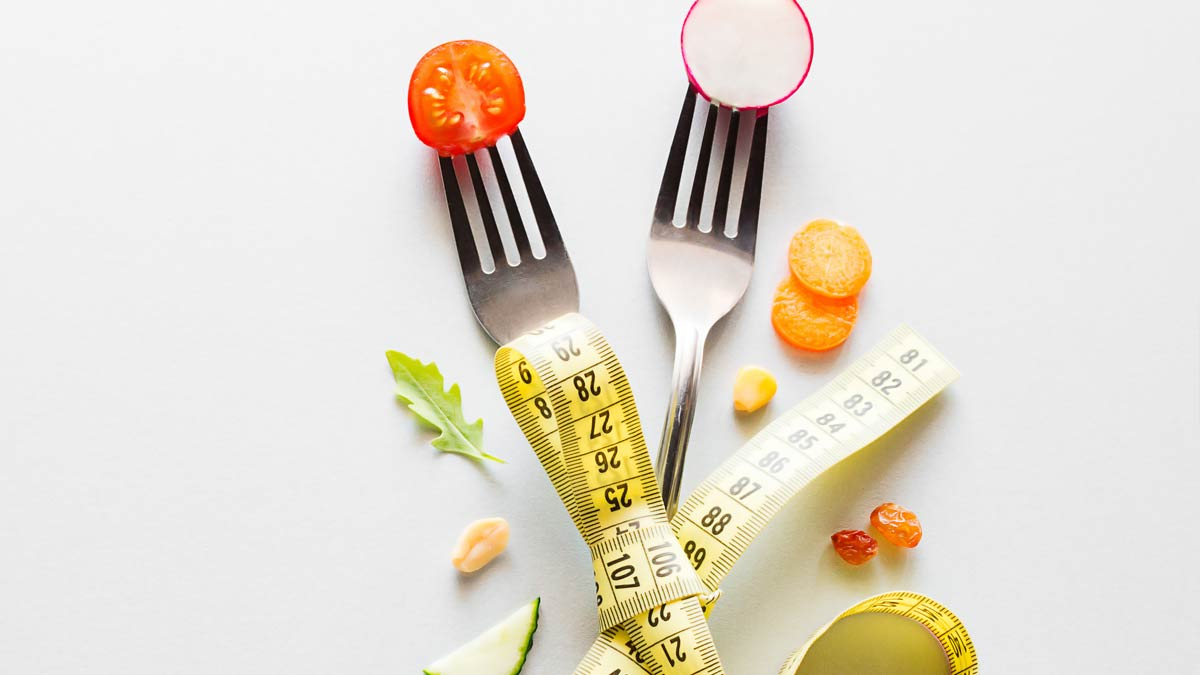 Diets: two forks and some healthy foods with a tape measure.