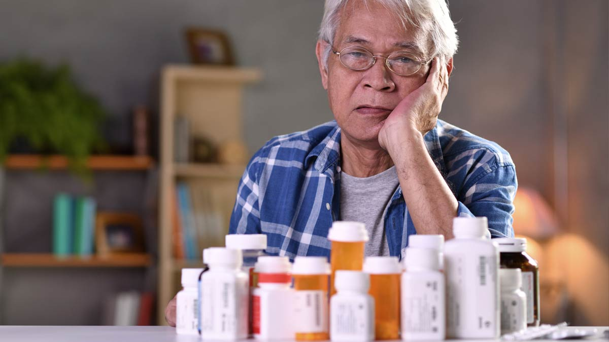 This senior gentleman almost seems depressed by the sheer number of medication bottles he has to deal with.