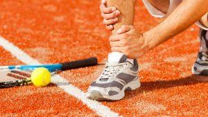 A tennis player grasping his shin.