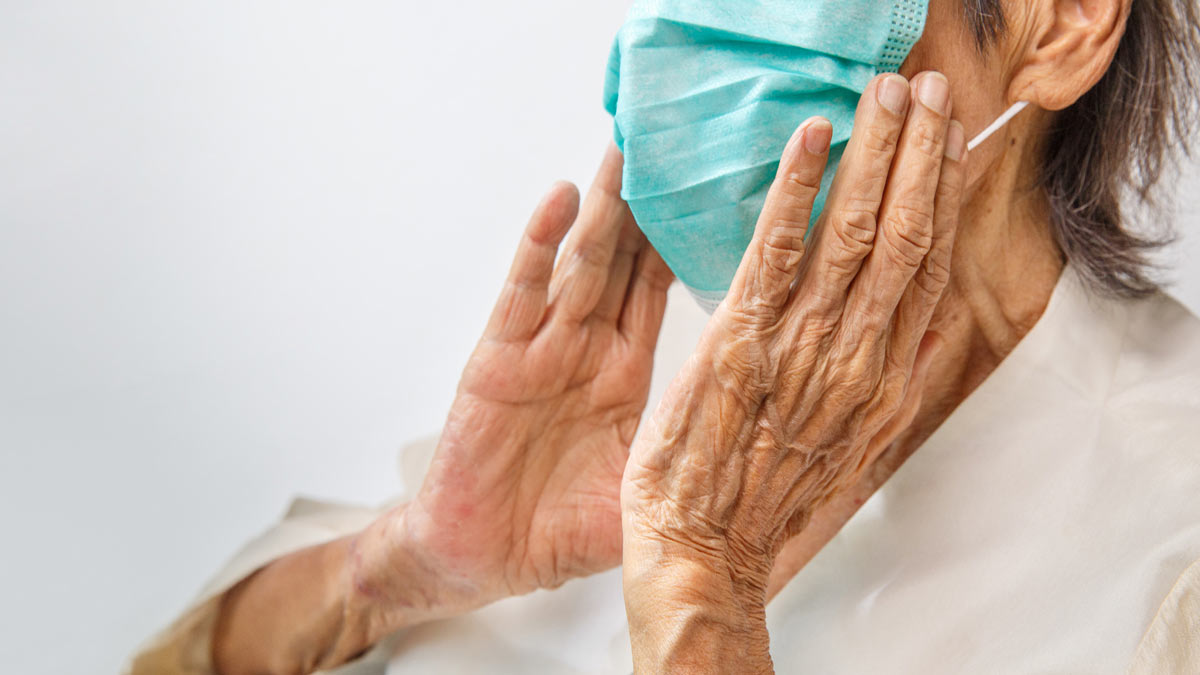 An elderly person uses a face mask for protection.