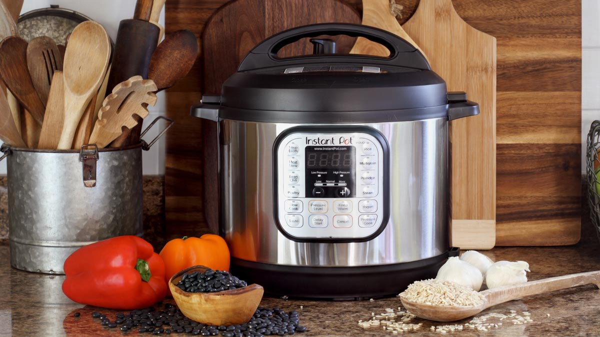 An Instant Pot, wooden utensils, bell peppers, black beans, rice and garlic.
