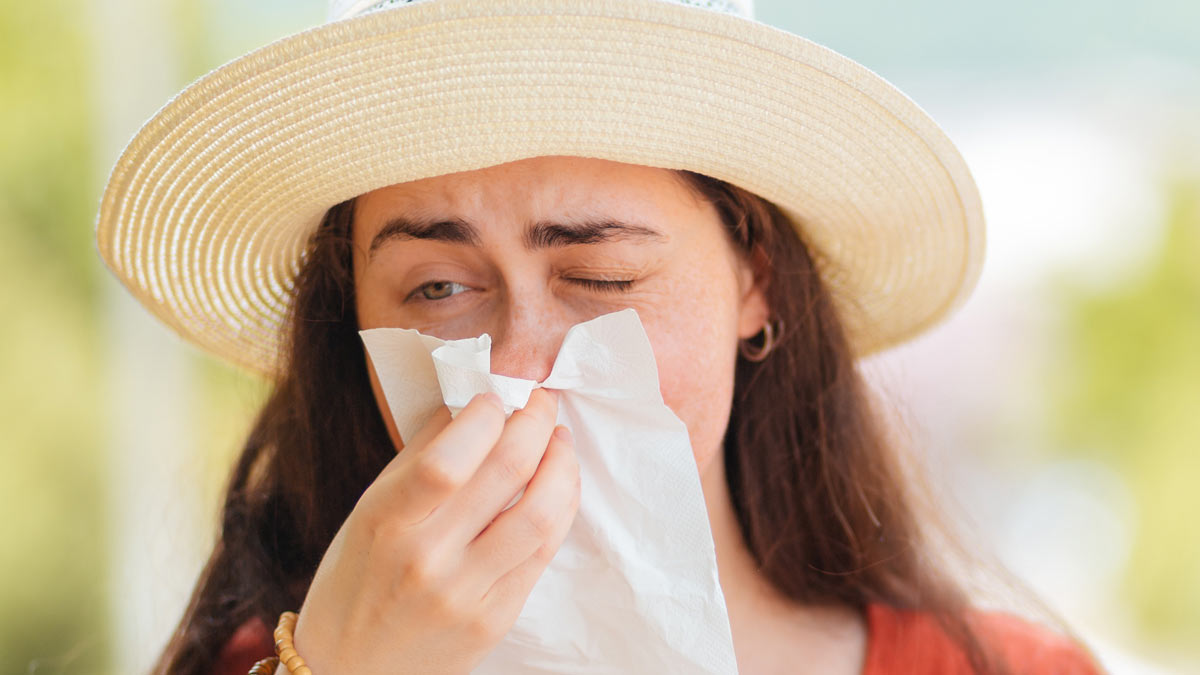 A girl with allergies blowing her nose