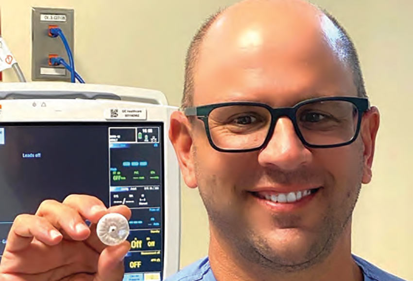 Electrophysiologist Darren Sidney, M.D., with Charleston Heart Specialists holding a WATCHMAN device.