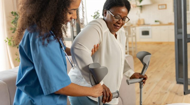 Post-surgery care: A nurse helps a patient with her crutches.