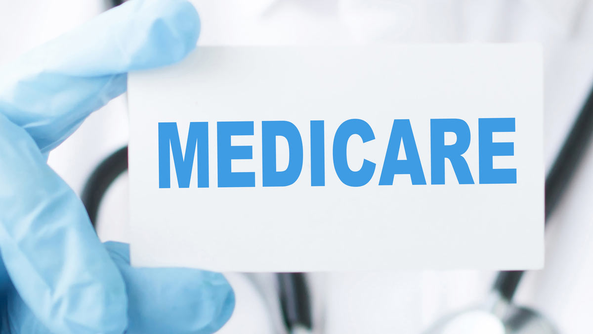 "A health care worker holding a business card that says ""MEDICARE"""