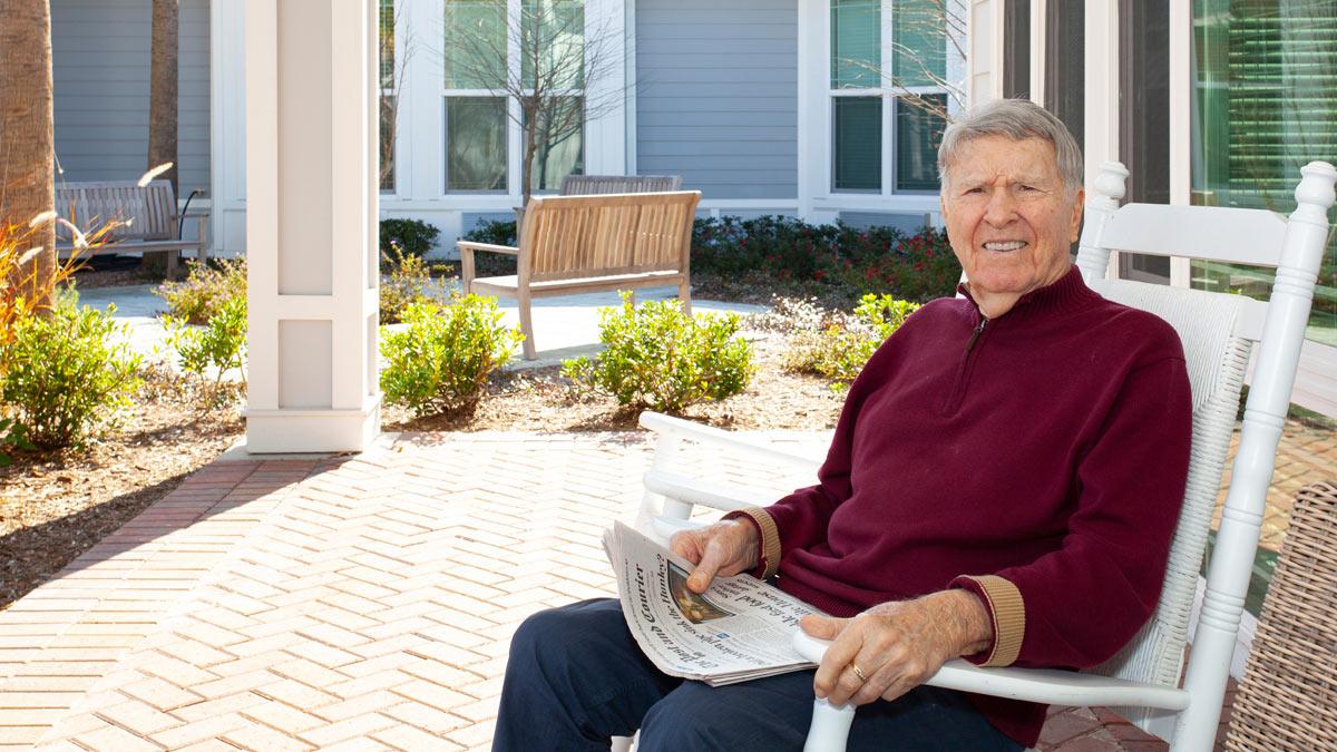 An older gentleman with his newspaper outdoors.