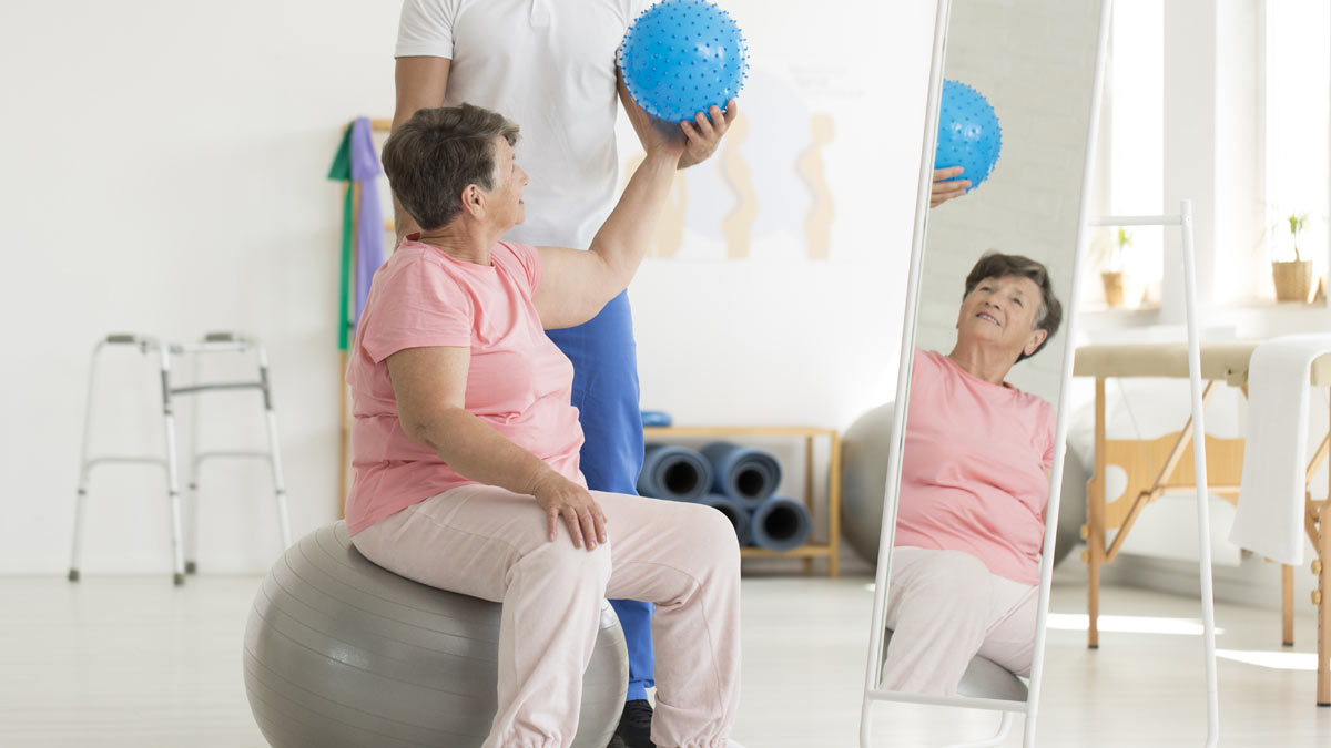 A woman on an exercise ball doing physical therapy exercises.