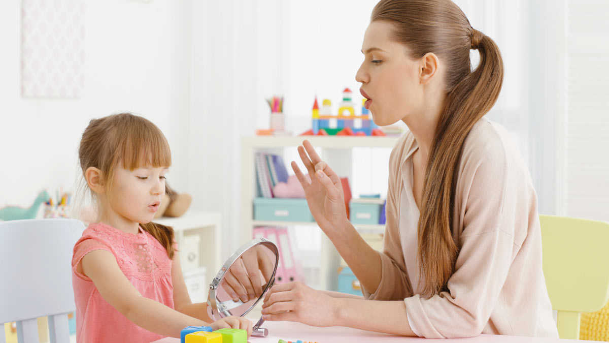A speech therapist working with a young girl.