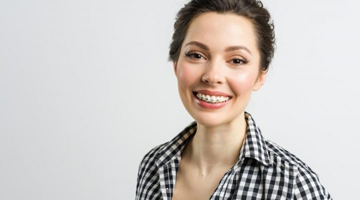 A woman with braces smiling.