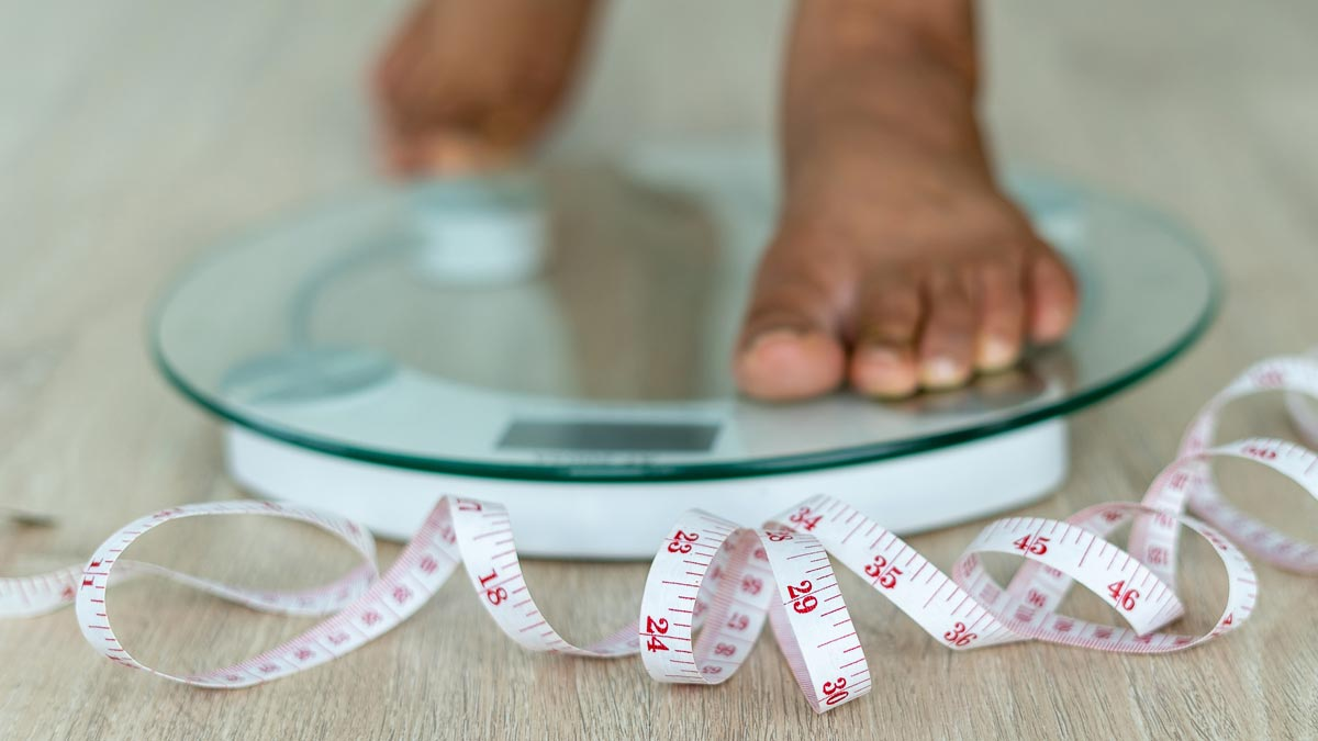 WEIGHT LOSS: An adult stepping on a scale.